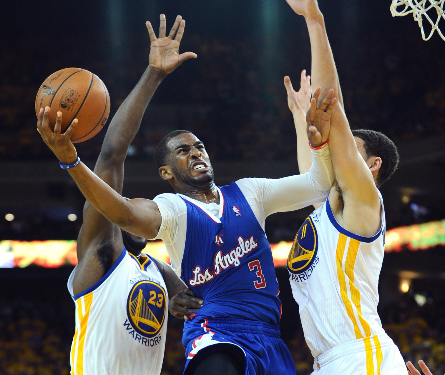 Clippers point guard Chris Paul drives between Warriors power forward Draymond Green, left, and guard Klay Thompson for a layup in the first half.