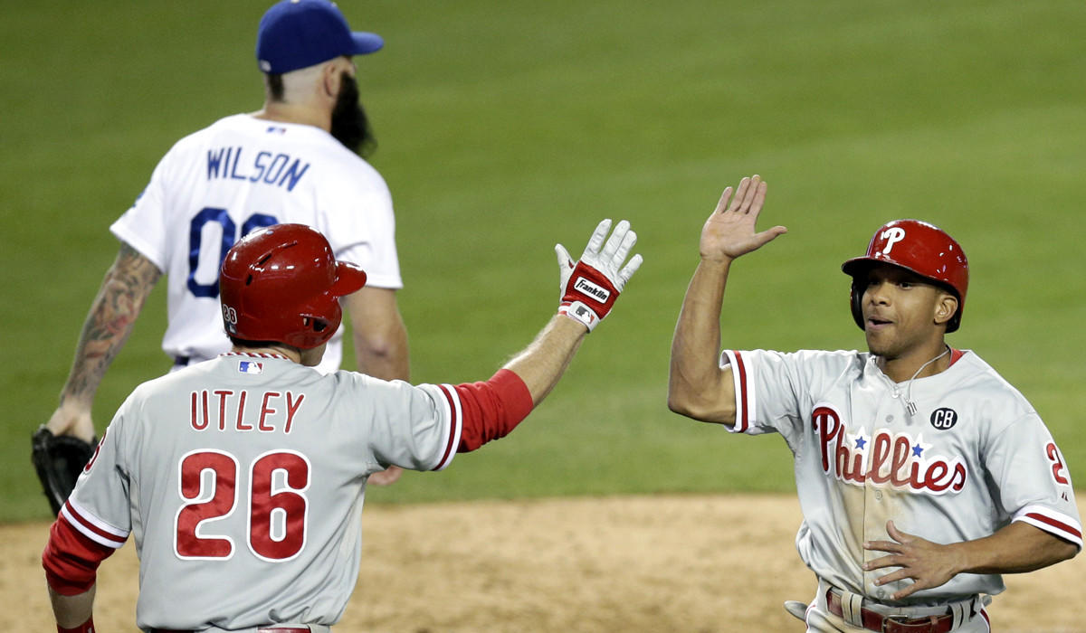 Phillies center fielder Ben Revere is greeted by second baseman Chase Utley after scoring on a two-run double by catcher Carlos Ruiz off Dodgers reliever Brian Wilson in the ninth inning Thursday night at Dodger Stadium.