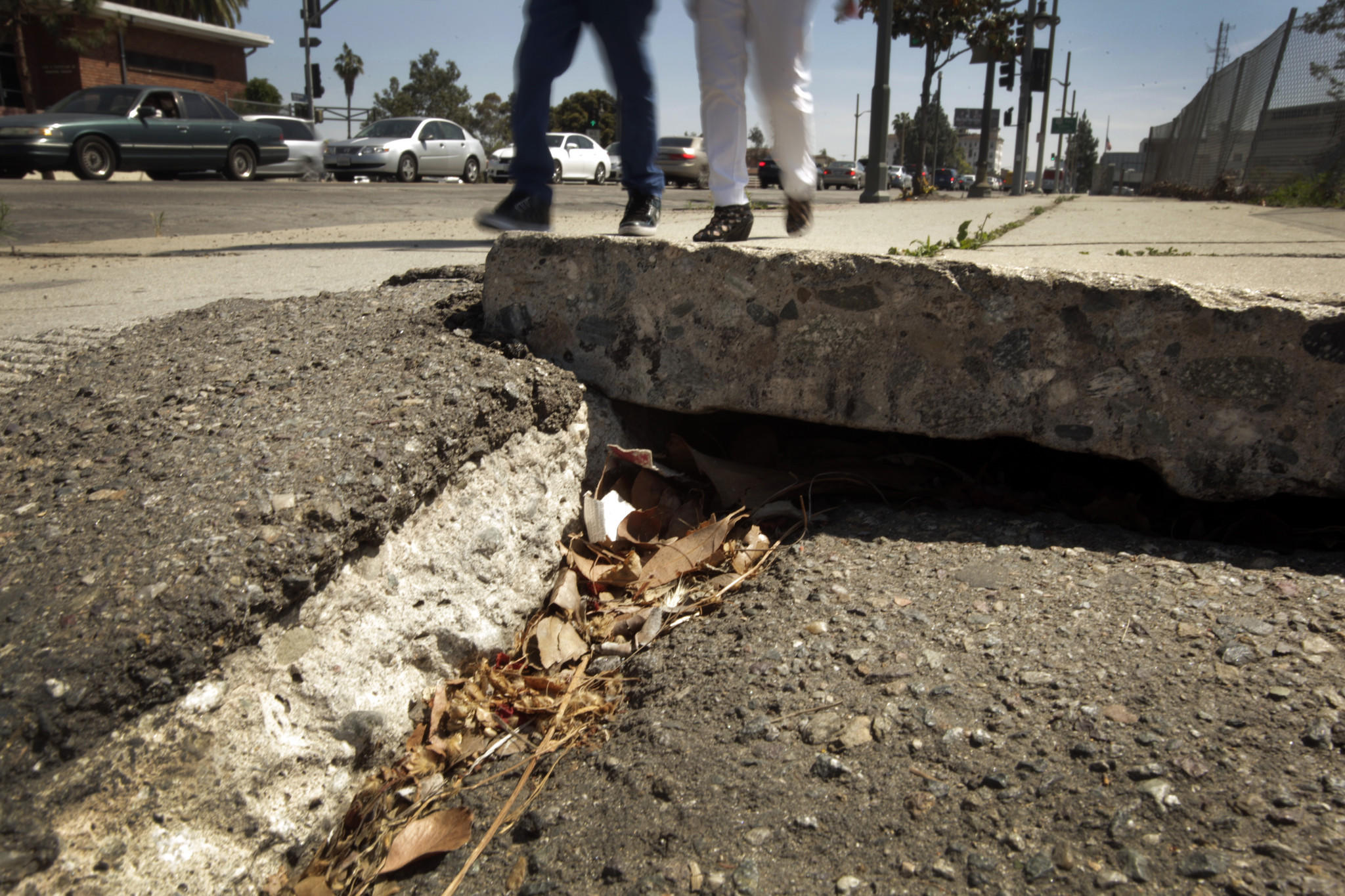 Two people navigate the sidewalk along Vermont Avenue where it meets the 101 Freeway.
