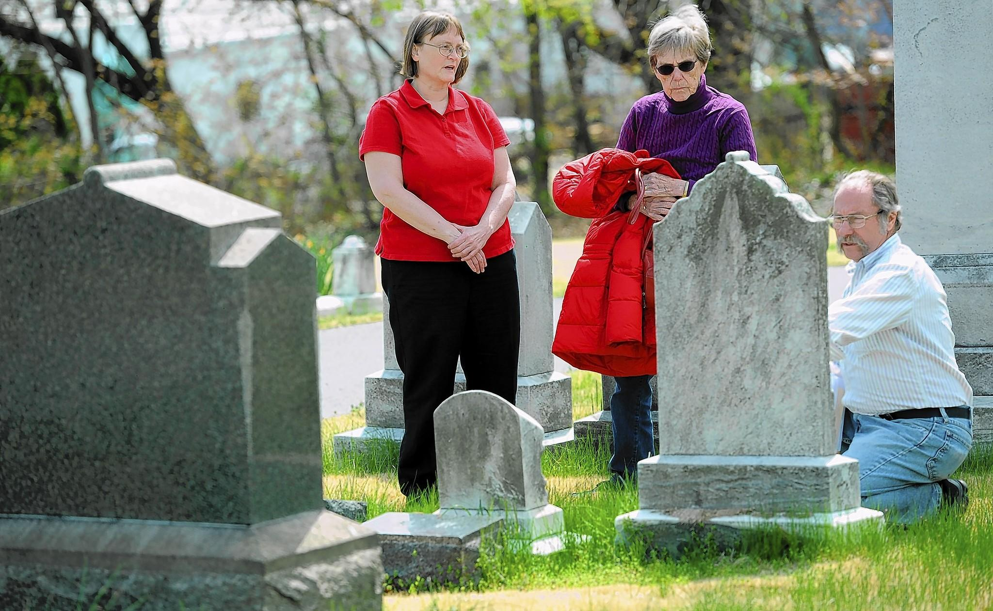 Chris Muldowney (from left), Jeanne Sears and Erik Nichols, members of the Lauraville Improvement Association, look at headstones as they walk through Immanuel Lutheran Cemetery.