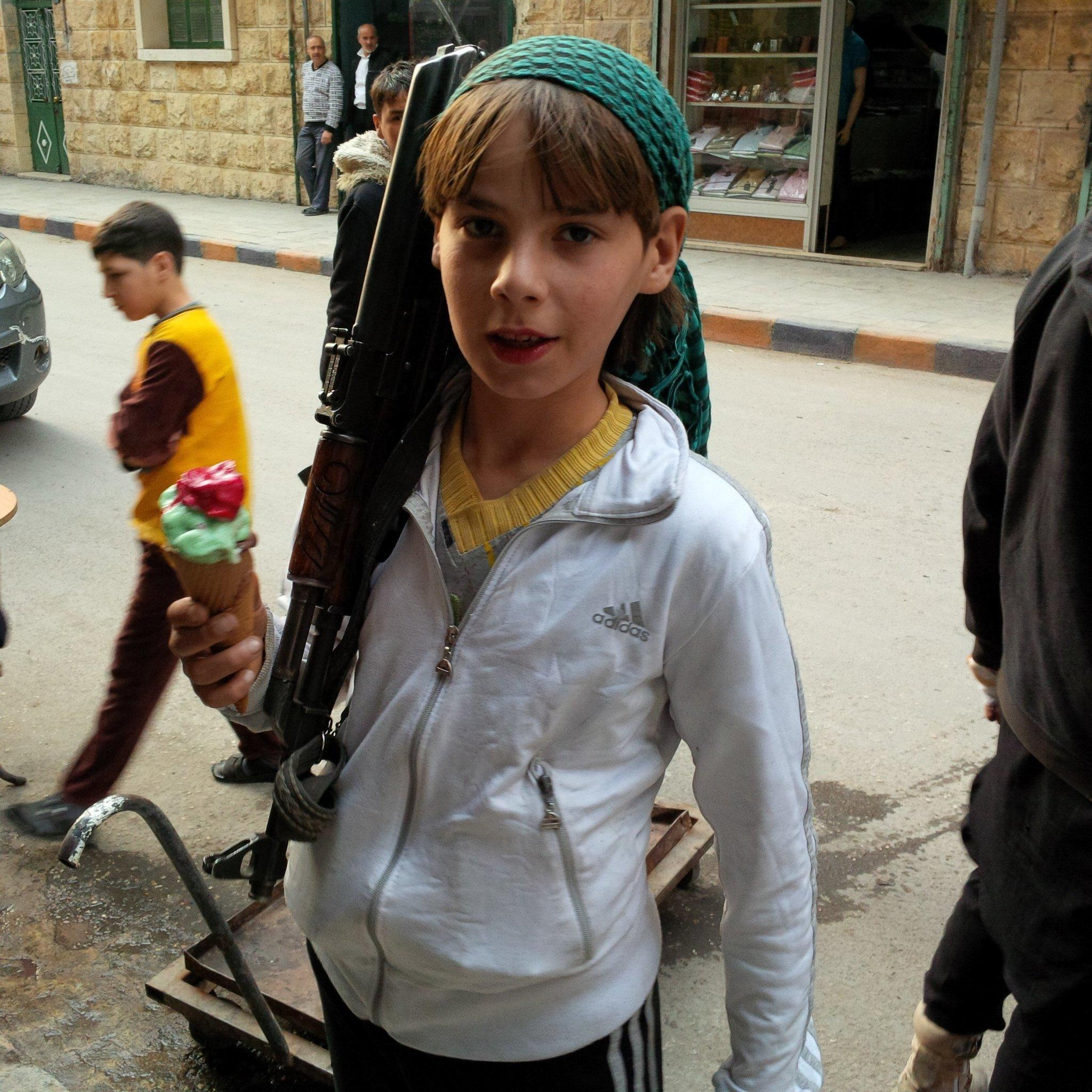 A boy standing with a rifle and an ice cream cone in Aleppo, Syria, says he is a fighter with the Suqoor Al Sham group, a member of the Islamic Front.