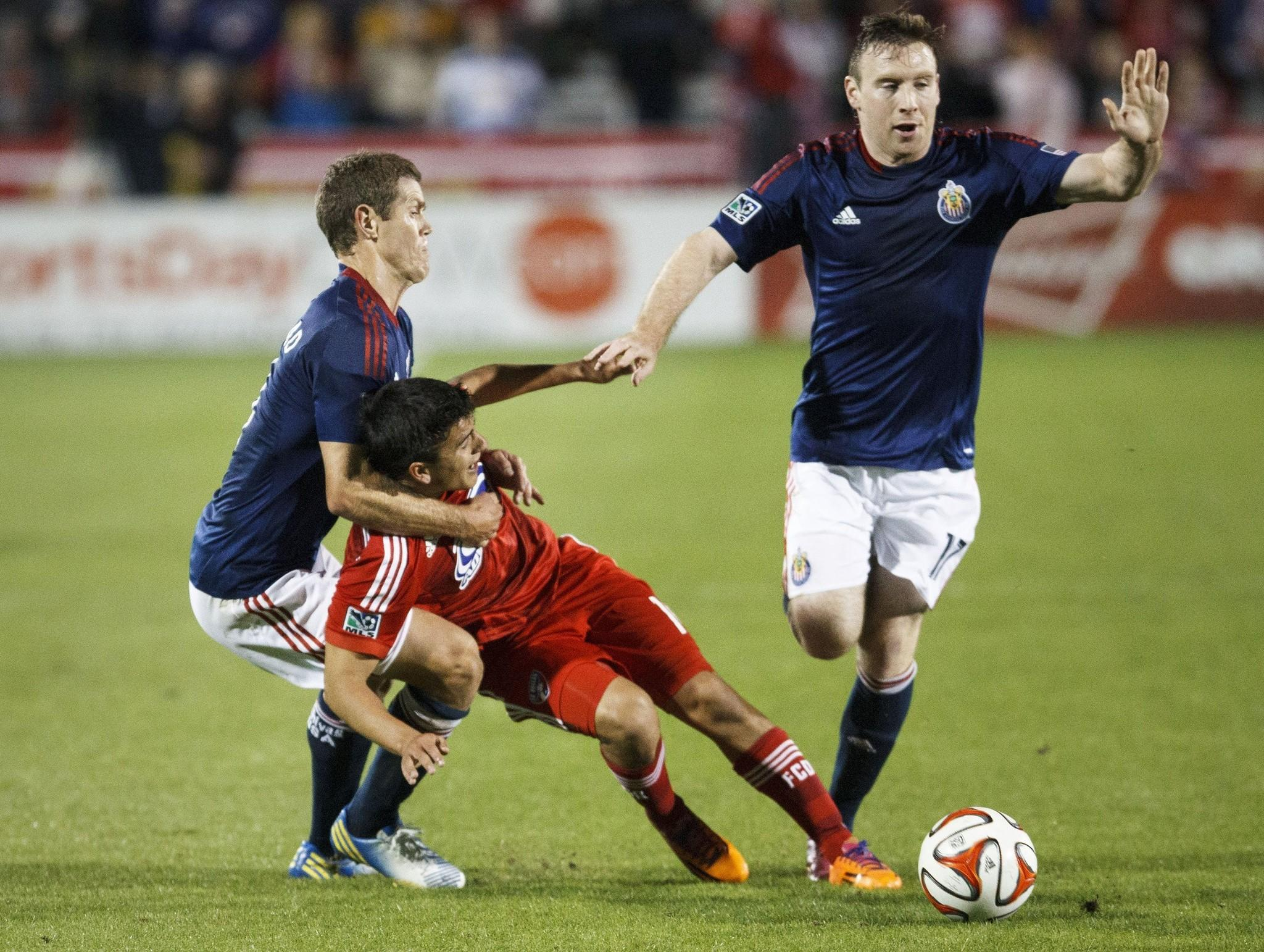 Chivas USA's Thomas McNamara, right, goes for the ball as his teammate Tony Lockhead, left, pulls down FC Dallas' Mauro Diaz during a match on March 22 at Toyota Stadium.