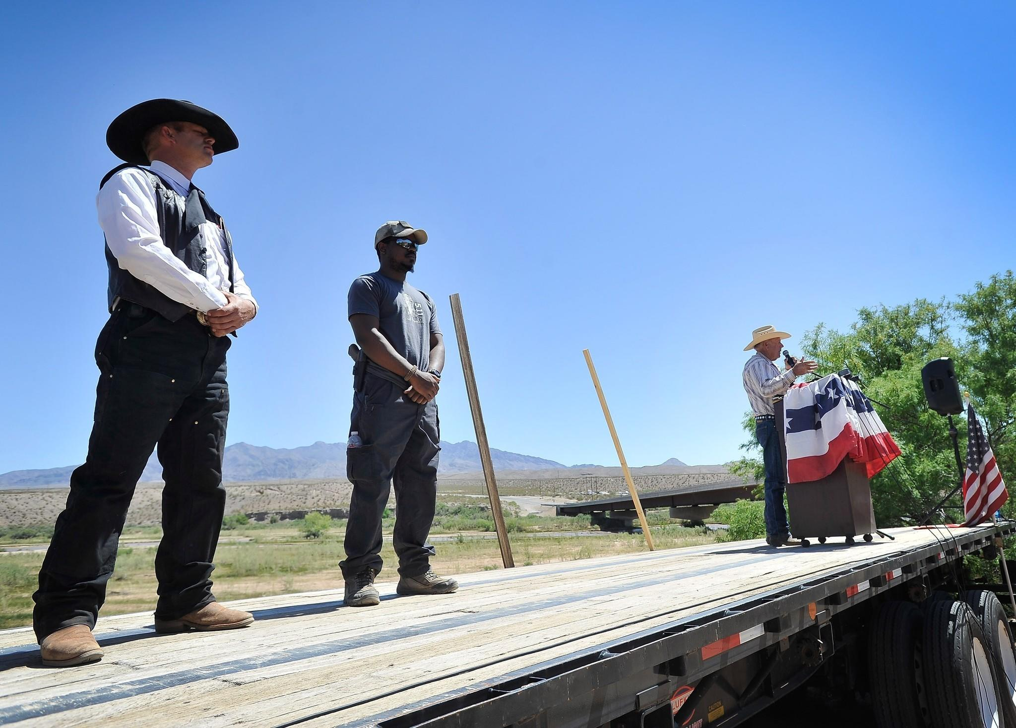 Rancher Cliven Bundy, with two supporters, speaks at a news conference Thursday near his ranch in Bunkerville, Nev.