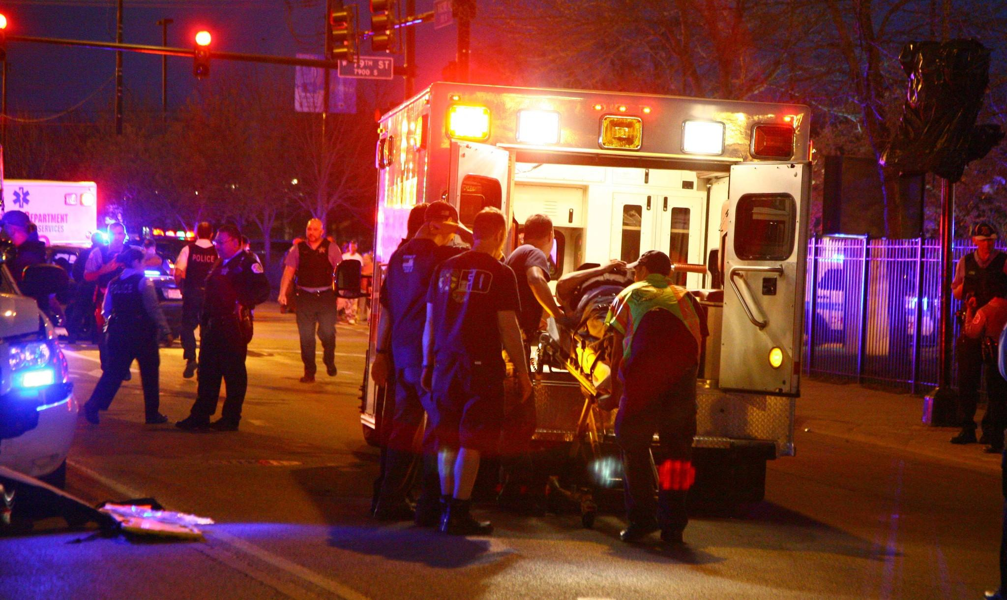 Chicago Fire Department medical personnel prepare an injured Chicago police officer to be taken by ambulance to a hospital following an accident at 79th and Racine involving two Chicago police vehicles and four police officers.