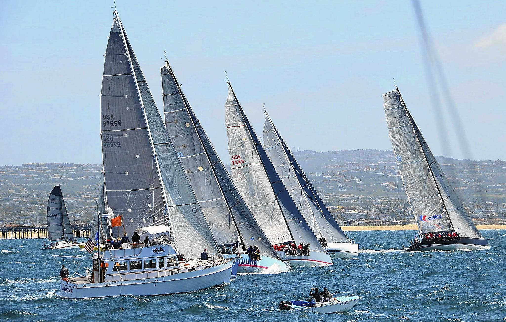 Racers and their crews take off in an even line at the start of the maxi class race during the 2014 Newport to Ensenada International Yacht Race on Friday.