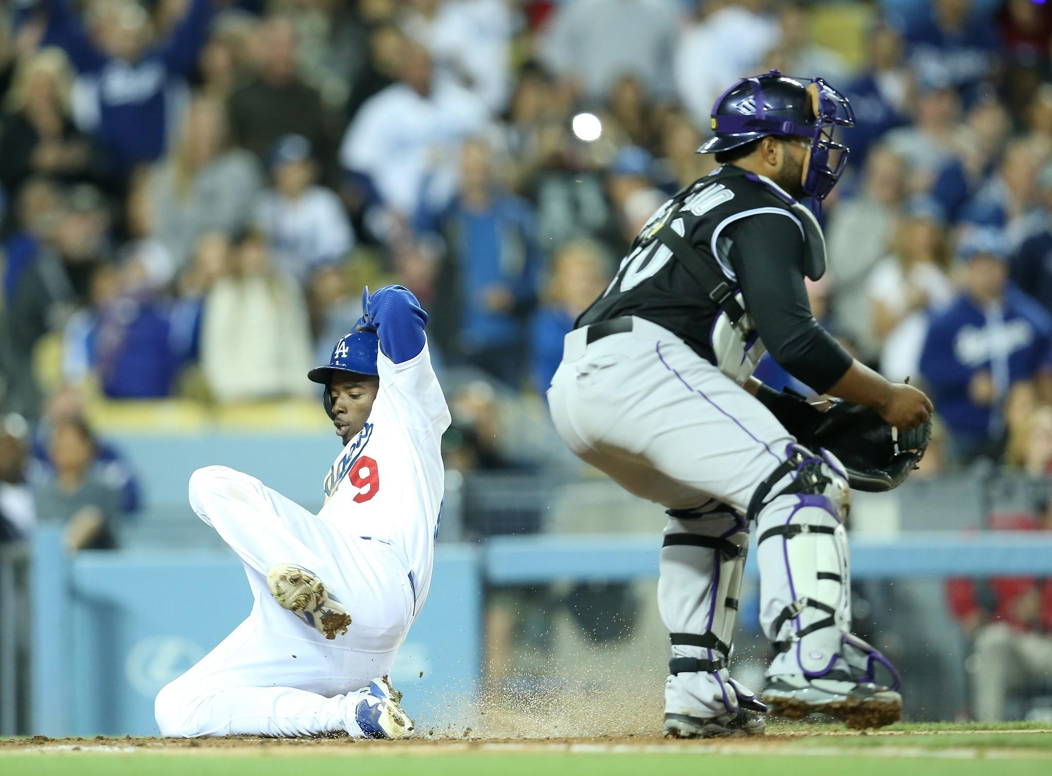 Dee Gordon slides past Colorado catcher Wilin Rosario to score in the third inning of the Dodgers' 5-4 loss to the Rockies on Friday at Dodger Stadium.