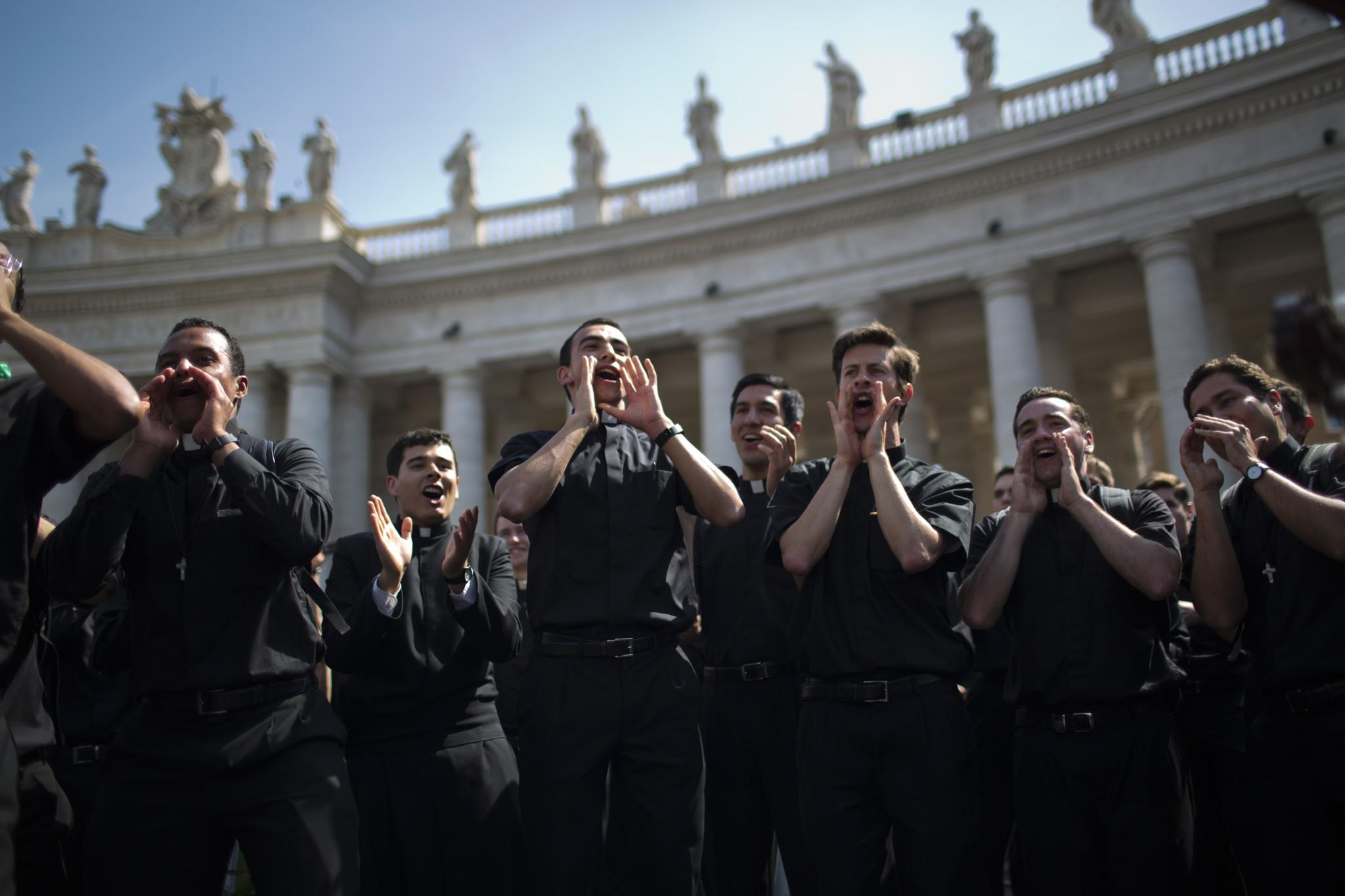 Priests sing and dance in St. Peter's Square at the Vatican on Saturday.