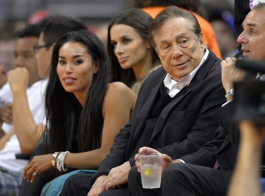 Los Angeles Clippers owner Donald Sterling, right, and V. Stiviano, left, watch the Clippers play the Sacramento Kings during an exhibition game earlier this season at Staples Center.