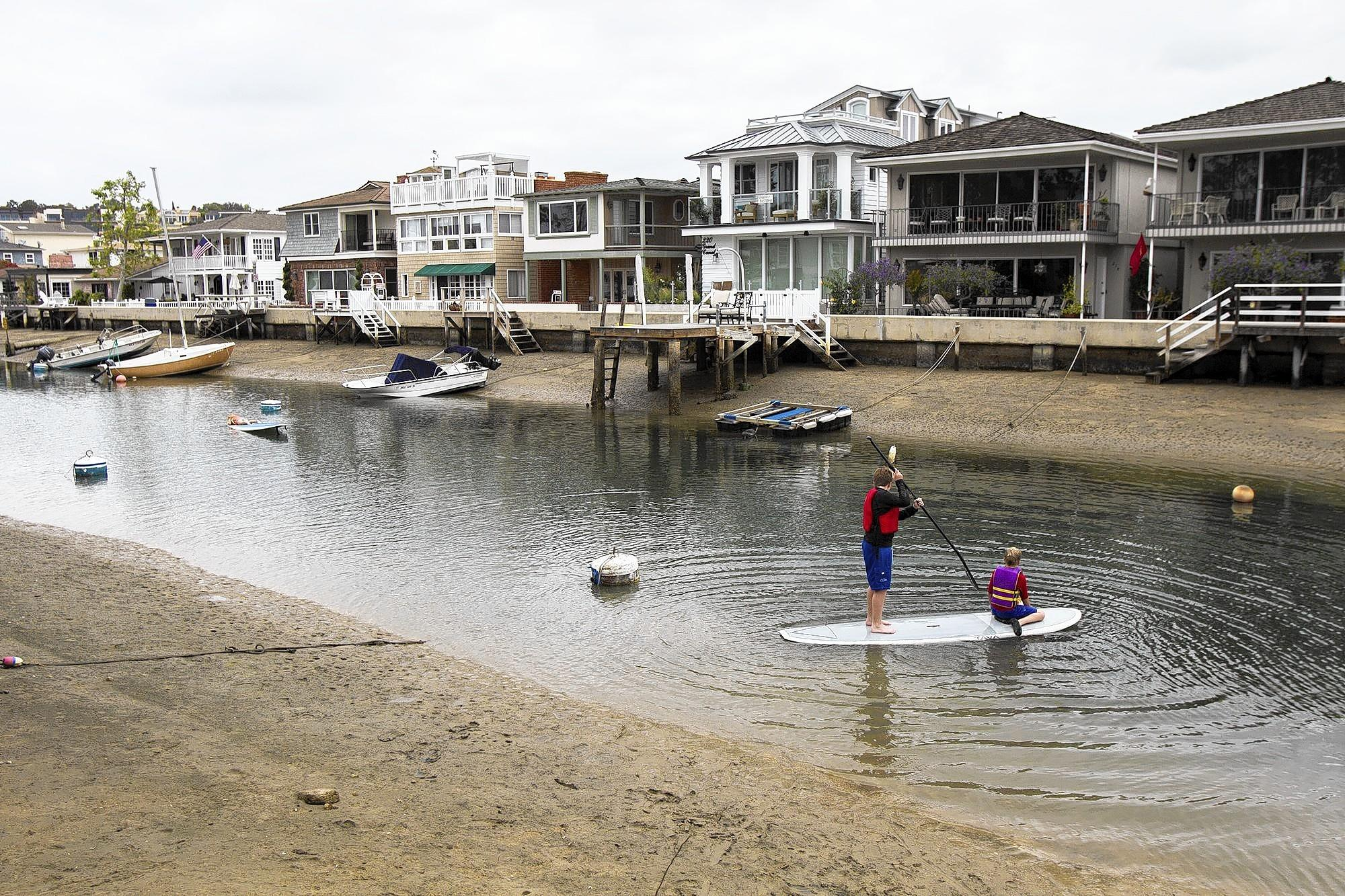 Charlie and Carson Geiling paddle through the Grand Canal that runs between Balboa Island on Tuesday. Residents are upset that the city stopped dredging the canal.