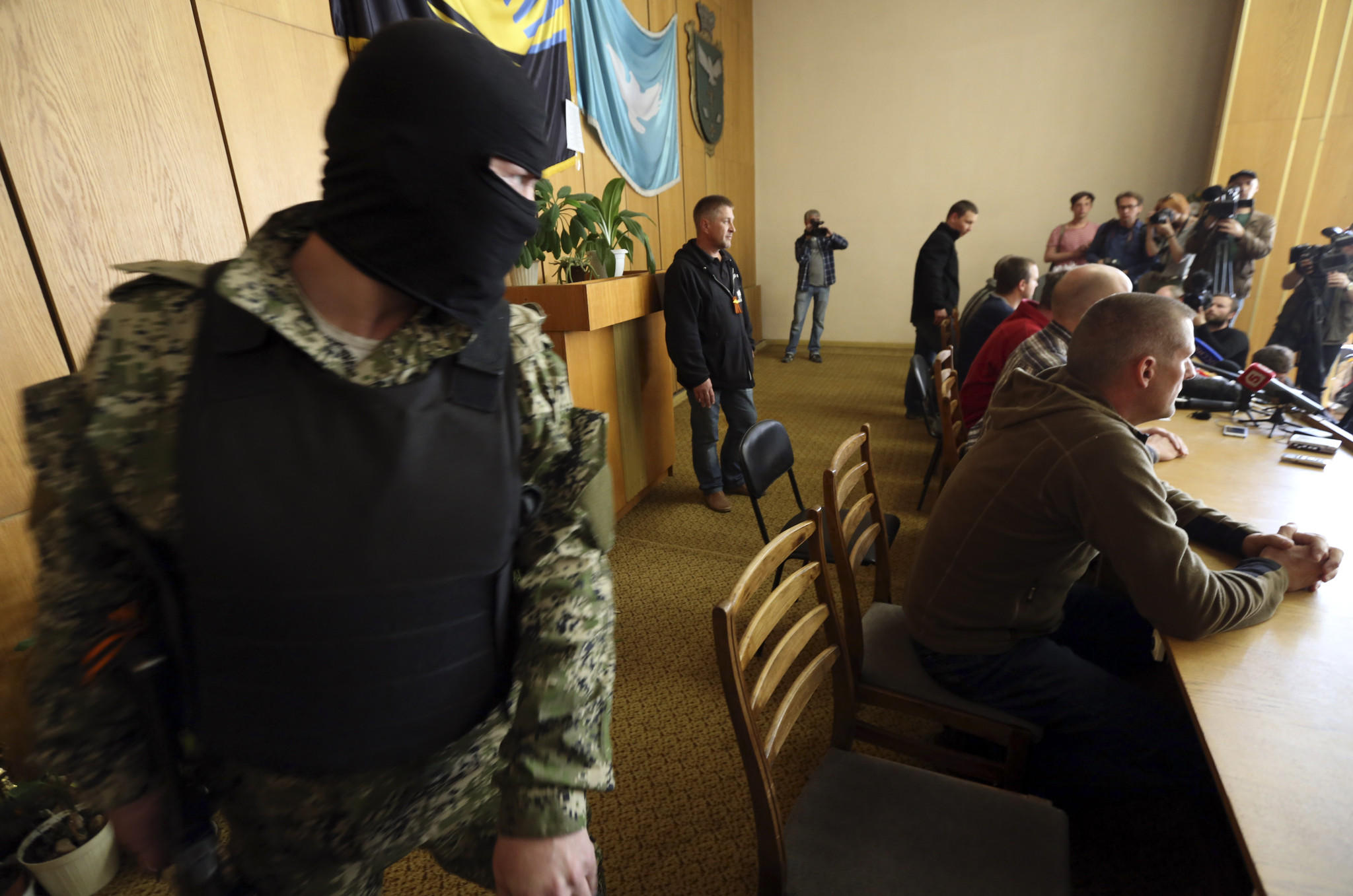 Armed pro-Russia militants watch over captive observers from the Organization for Security and Cooperation in Europe just before the start of a news conference in Slovyansk, Ukraine, on Sunday.