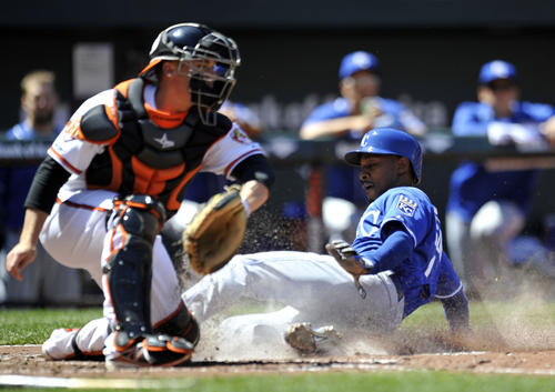 Kansas City Royals center fielder Jarrod Dyson, right, scores on a sacrifice fly in front of Orioles catcher Steve Clevenger in the third inning at Camden Yards.
