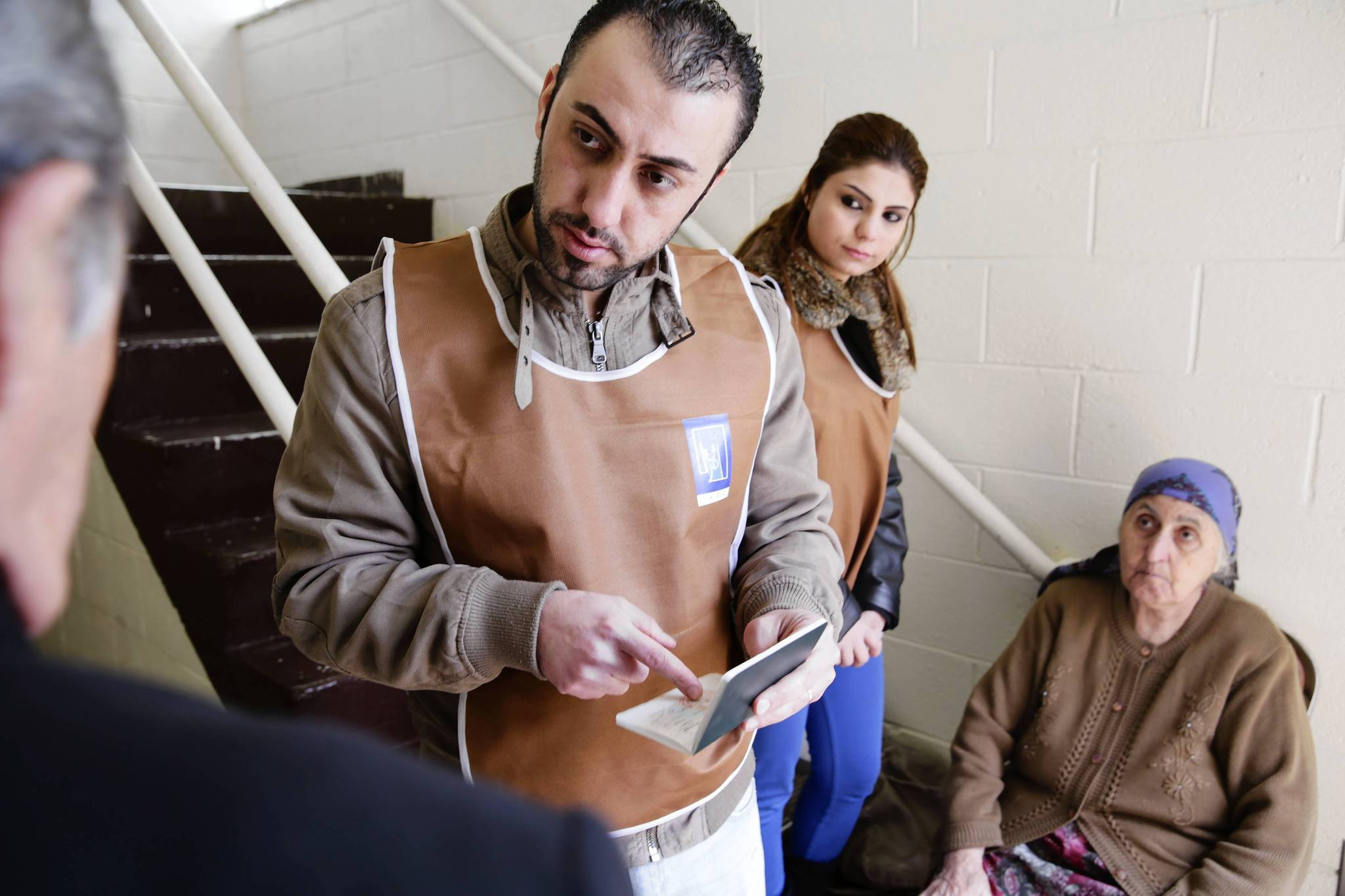Election worker Robert Yohanna, 2nd from left, checks the IDs of Iraqi citizens wishing to vote in the Assyrian National Council of Illinois in Skokie. Iraqis will vote for governors and members of parliament.