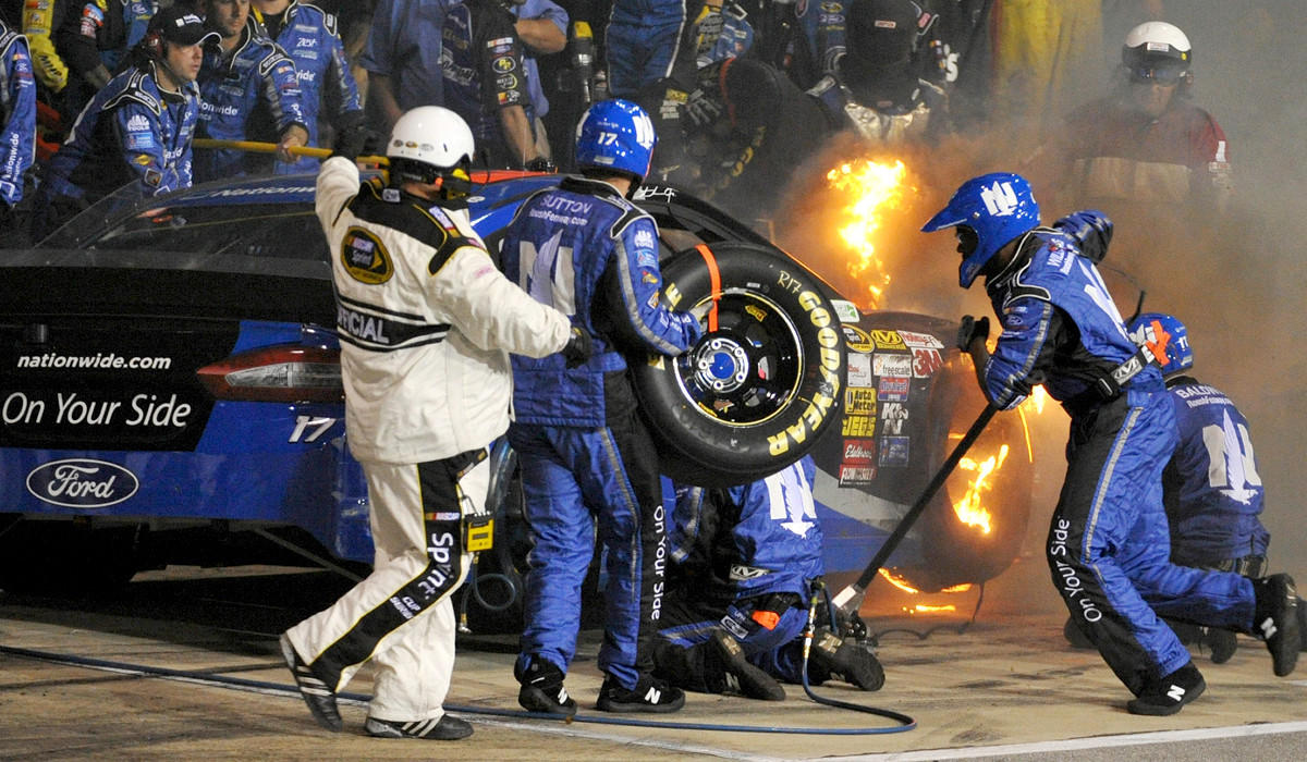 The car of NASCAR driver Ricky Stenhouse Jr. pits while on fire during the Sprint Cup Series Toyota Owners 400 at Richmond International Raceway on Saturday night.