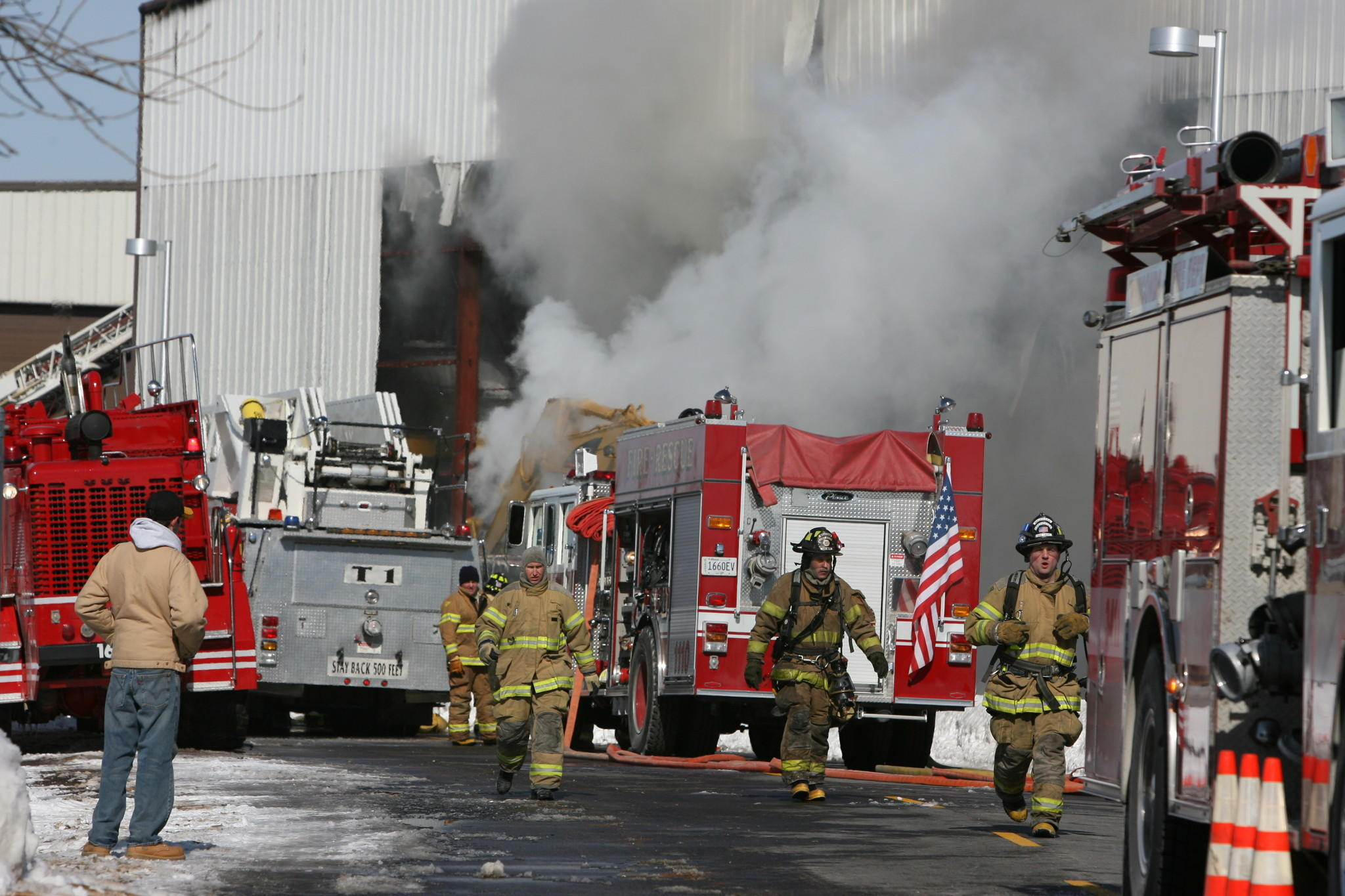 Firefighters run for more hoses as they work a four-alarm fire with foam (smoke appearance) at a boat storage building at Skipper Bud's in Winthrop Harbor, Ill.