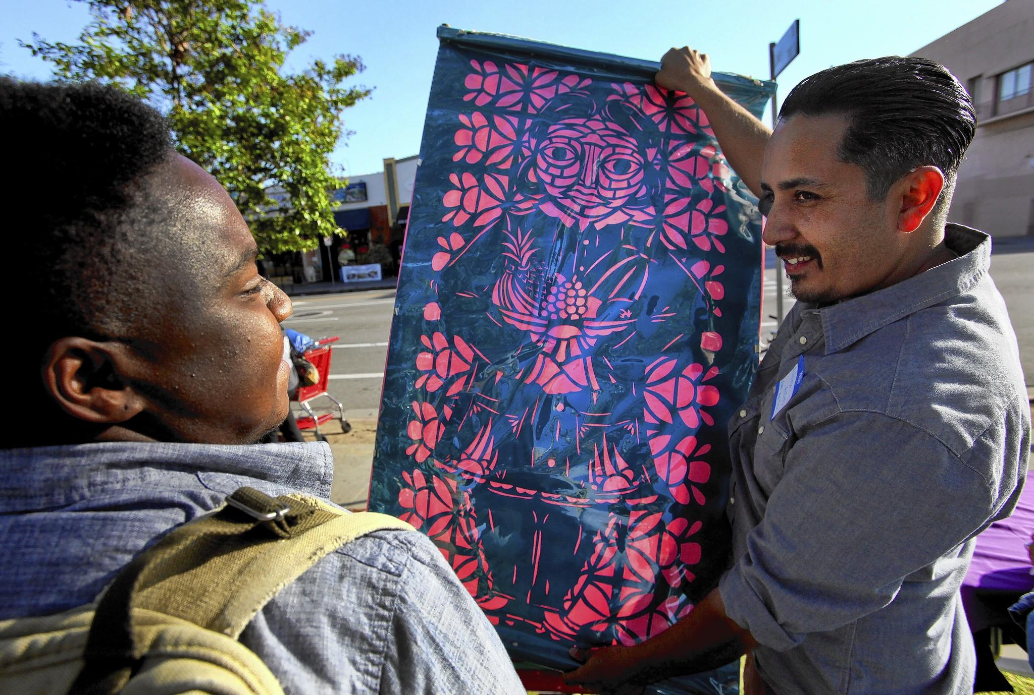 Alfonso Aceves, right, lead artist for L.A. Commons, holds up a papel picado, a traditional Mexican cutout. Students will create an art installation using papel picado bunting for MacArthur Park.
