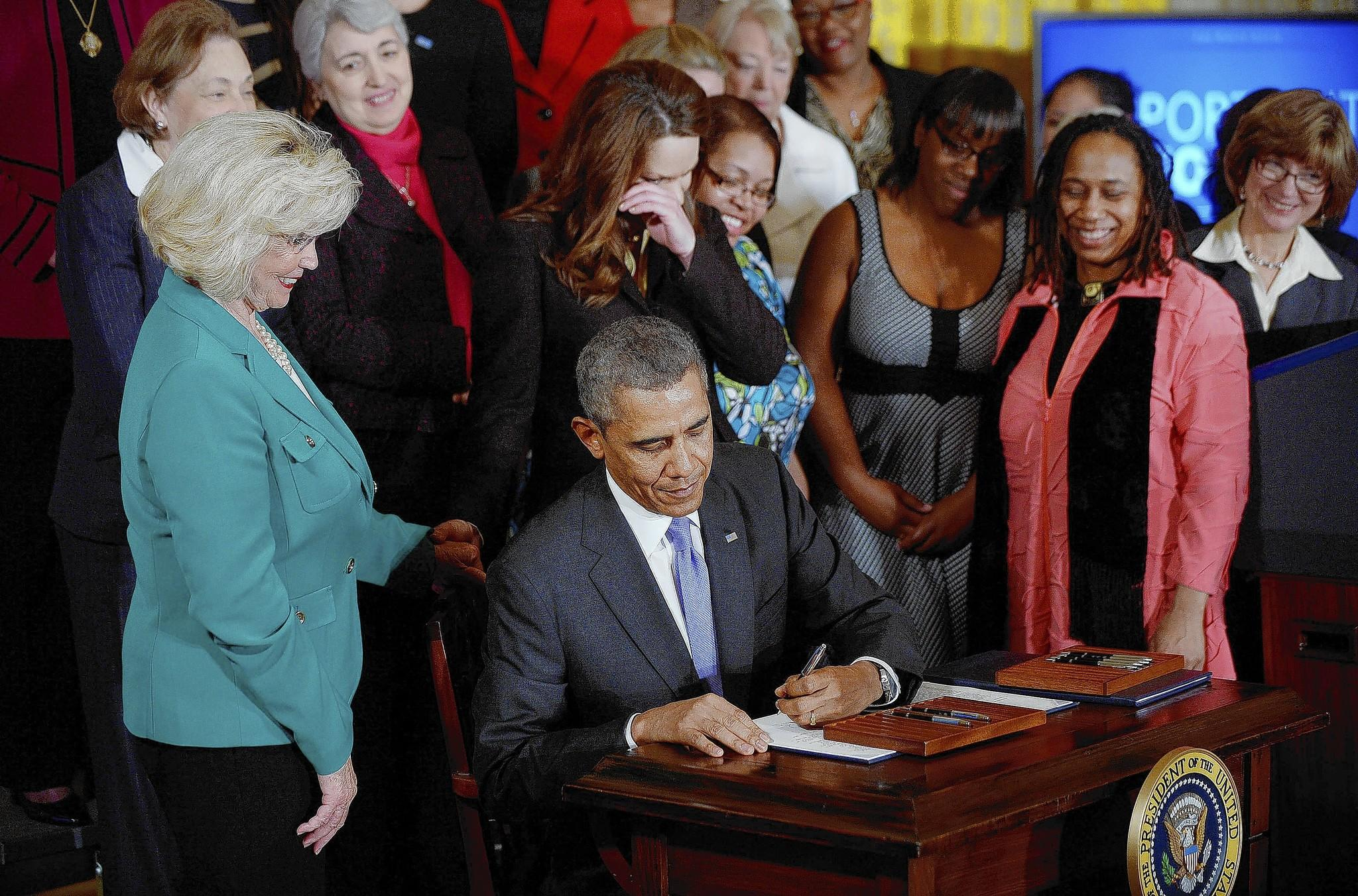 President Barack Obama signs executive orders on equal pay at the White House on April 8 as women including Lilly Ledbetter, left, look on.