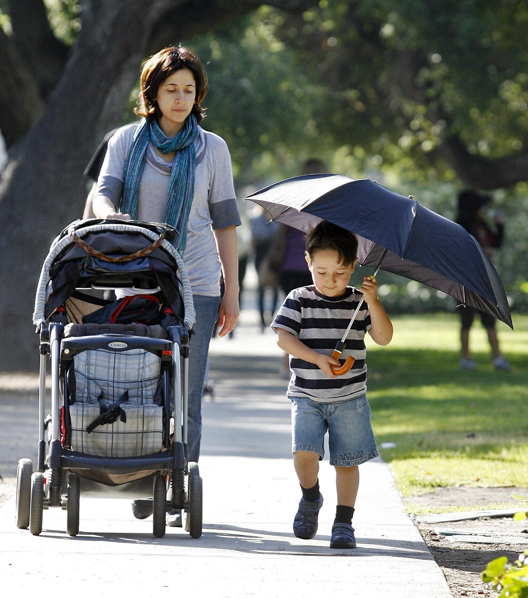 File Photo: Edgar Galstyan, then 3, holds an umbrella, partly to keep from the sun, but more for play, as he walks home with his mom Lusine Tsaturyan after making the morning drop off of a sibling at R.D. White Elementary School in Glendale on May 9, 2012.