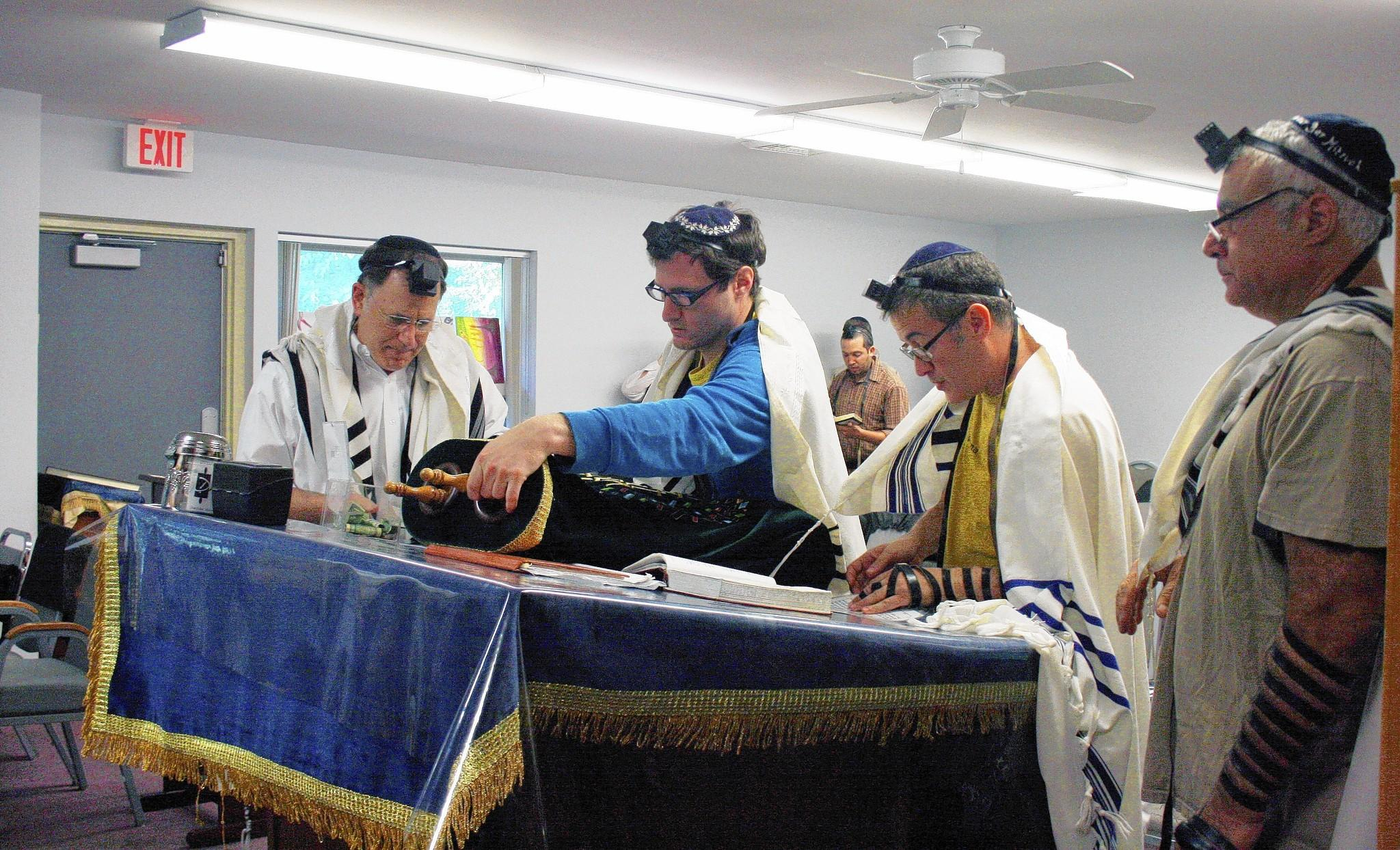 Darchei Noam of Glenbrook member Shaya Avner, center, uncovers one of the congregation's two Torah scrolls during a morning service on Aug. 1. The congregation is going to start construciton on its new synagogue soon.