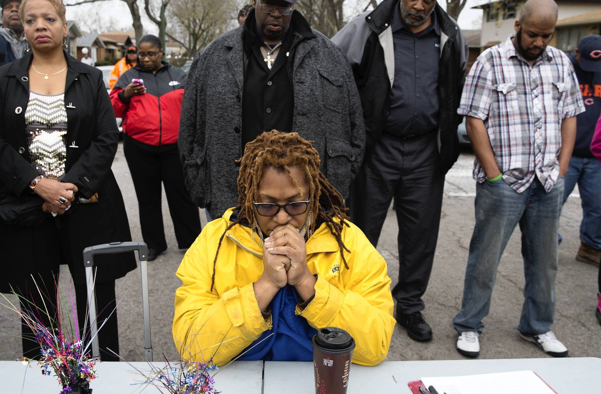 Residents pray at a rally against gun violence in the West Pullman neighborhood after the shooting death of community activist Leonore Draper.