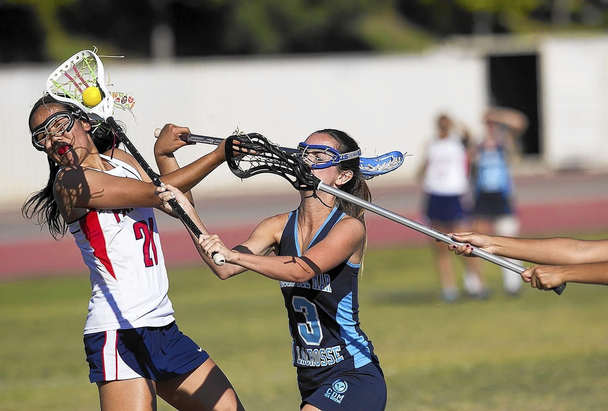Corona del Mar High's Kacie Kline takes a shot, as Beckman's Luna Tsujimoto attempts to block her during a Pacific Coast League game on Monday.