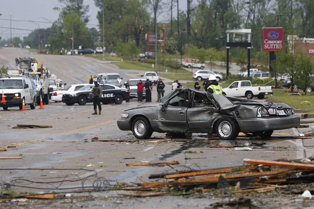 Emergency personnel walk along North Gloster Street after a tornado went through Tupelo, Miss., on Monday.