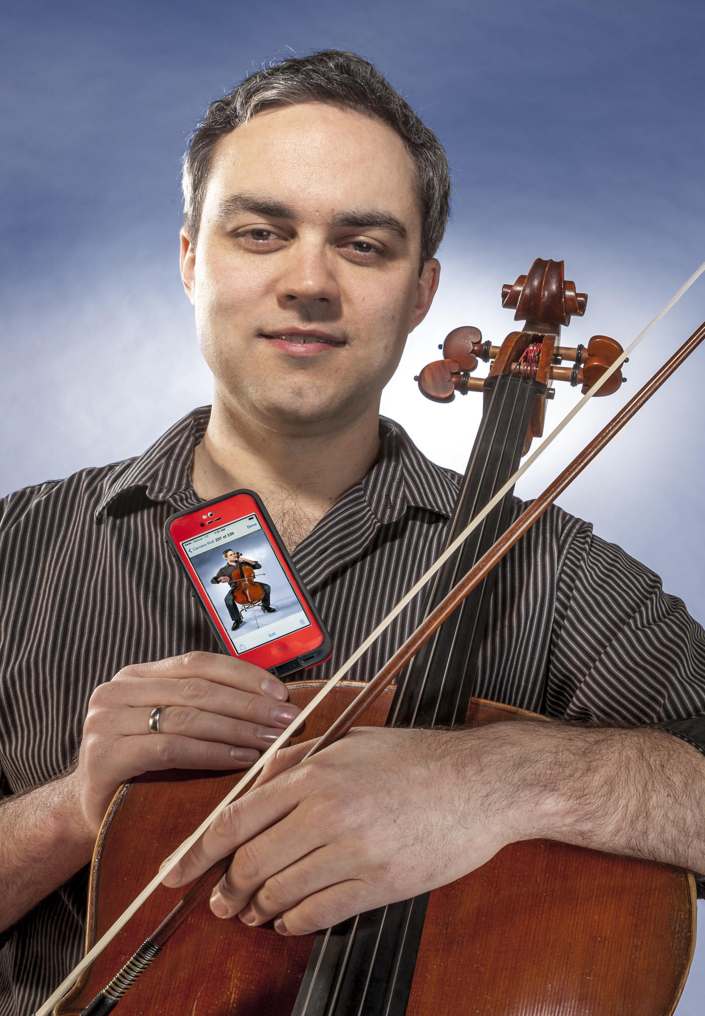 Russell Rolen, cellist for Spektral Quartet, poses with his cello and an iPhone featuring his likeness.