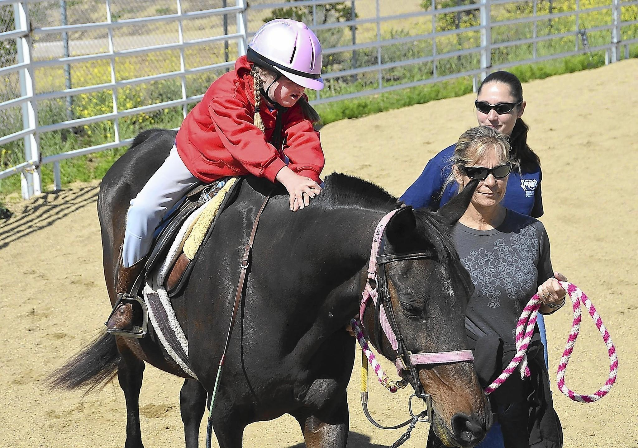Ten-year-old Julia Kelly holds onto Kattie during her riding class at the Huntington Beach Therapeutic Riding Center on Saturday in preparation for the center's annual Derby Day fundraiser.
