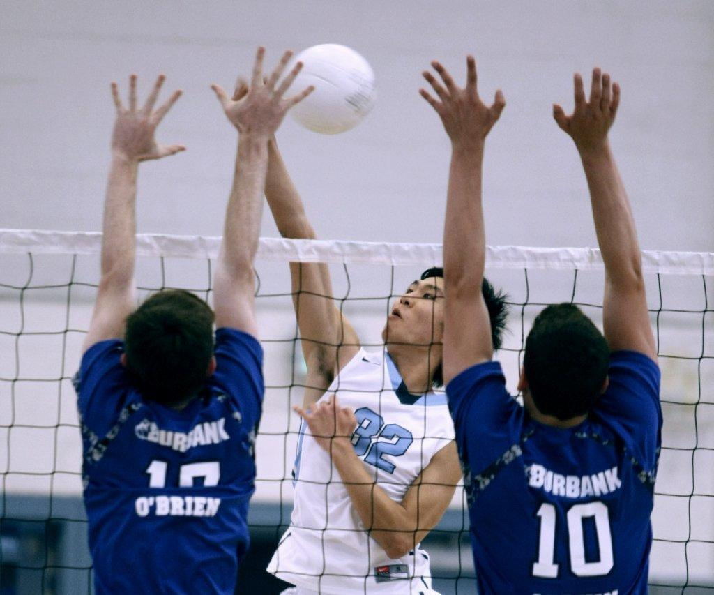 Crescenta Valley High School's Chris Yi (center) spikes the ball during a Pacific League match versus visiting Burbank on Tuesday, April 29, 2014. (Raul Roa/Staff Photographer)