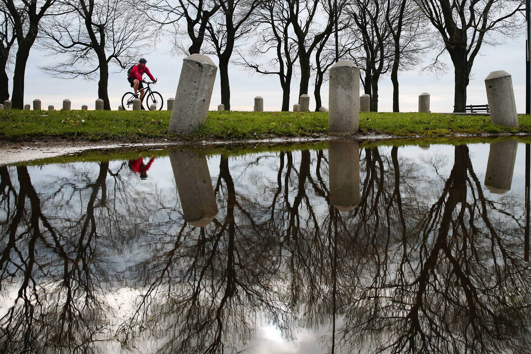A cloud filled sky is reflected in a puddle near Fullerton Street Beach in Chicago as a cyclist rides south along Lake Michigan.