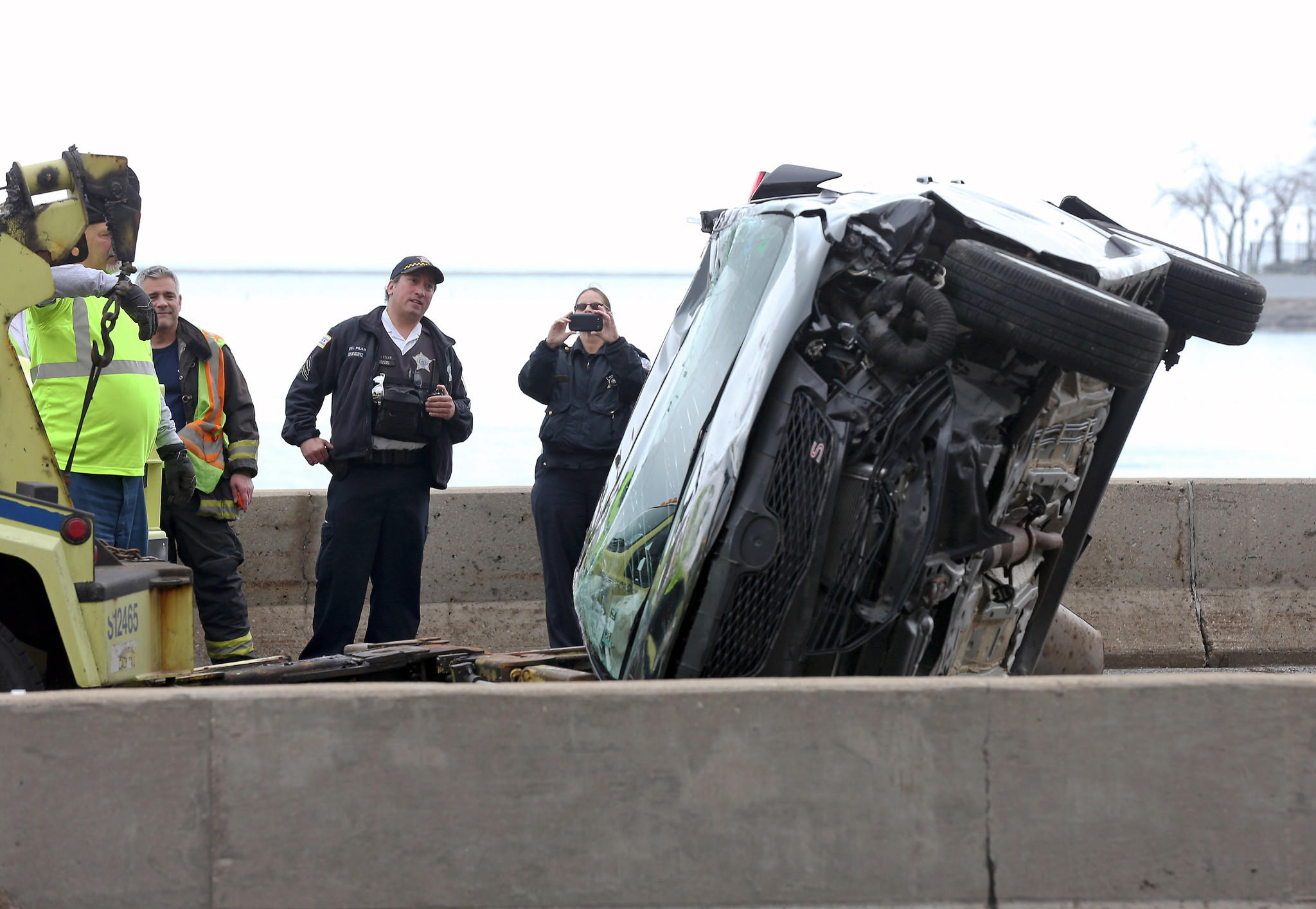 Police officers watch as a car is uprighted after a rollover crash on the northbound lanes of Lake Shore Drive.