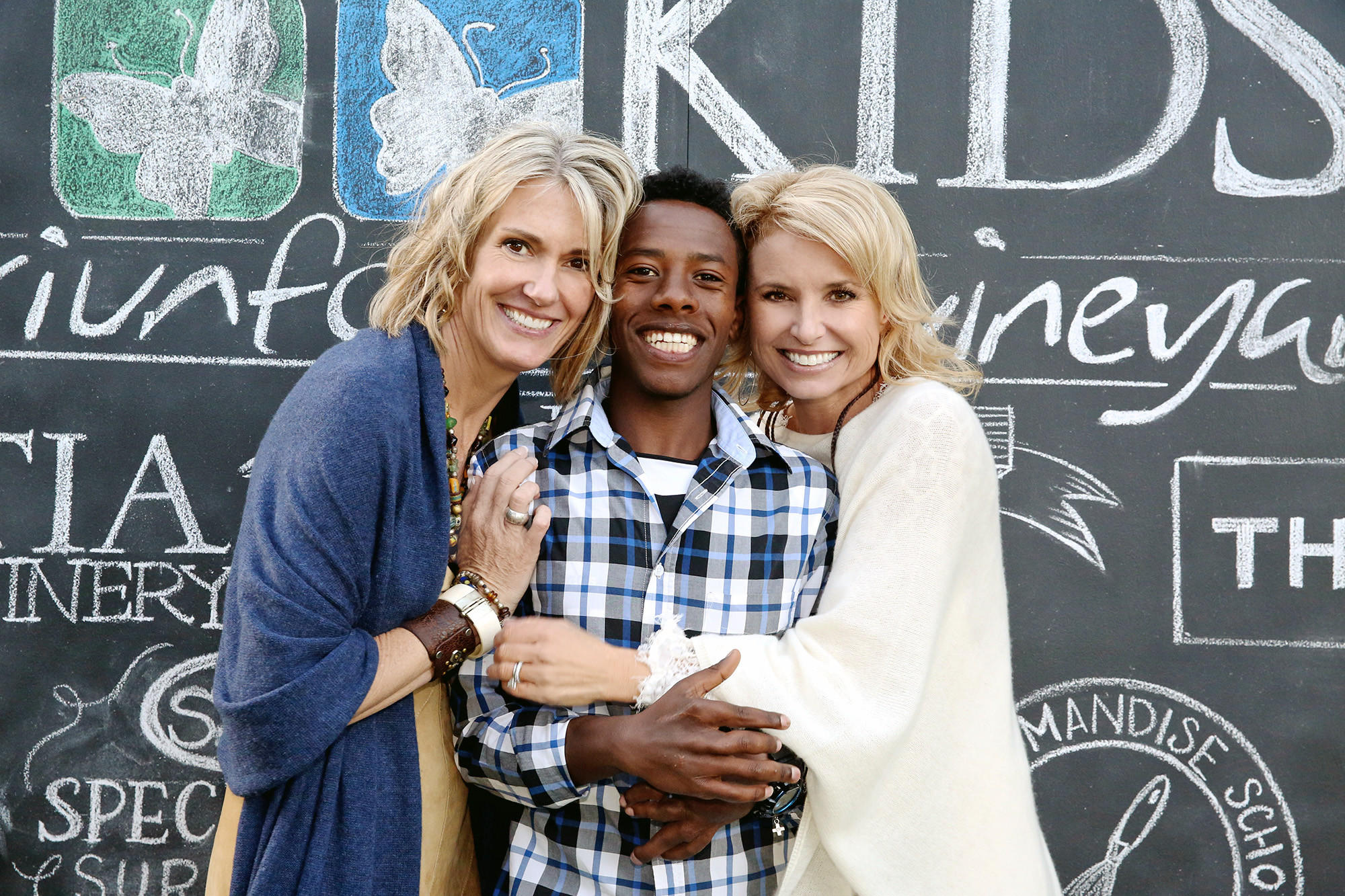 Left, Laurie Dugan, president of the Mending Kids board of directors, and her event co-chair Brooke Bohm with a young man from Ethiopia named Werkneh who has received treatment from Burbank-based organization Mending Kids for painful, 10-pound tumors on his hands.