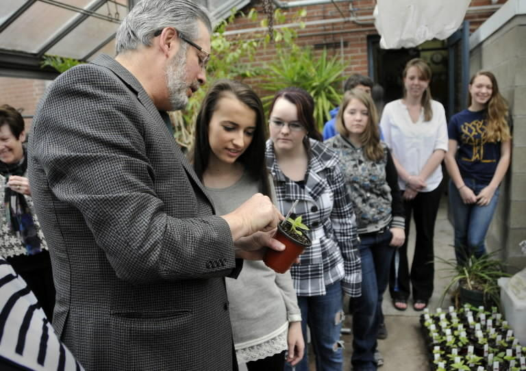 "Dr. William Petit talks about the Four O'Clocks flowers growing in the Glastonbury High School greenhouse with students Wednesday. The Glastonbury High School Future Farmers of America class has been raising and growing 2500 ""Four O'Clock"" flowers to raise money for the Michaela's Garden Project, a fund raiser for the Petit Foundation. Speaking with Dr. Petit are, from left: Nermina Mehmedovic, soph, Katie Libbey, sr, and Carissa Gaghan, sr."
