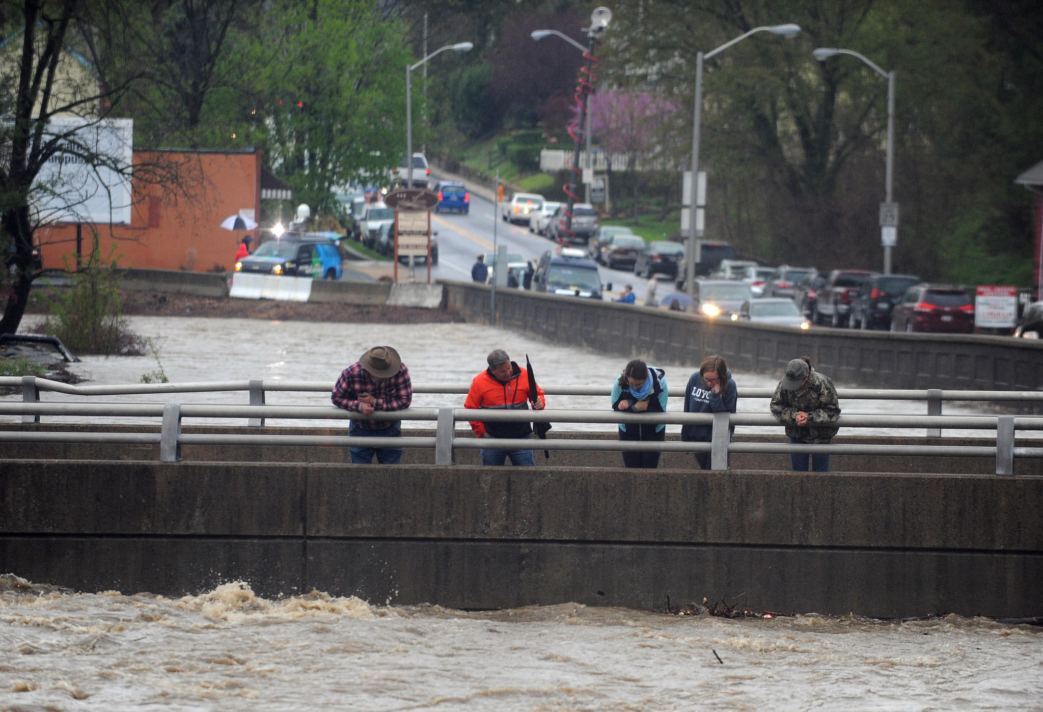 Onlookers watch the high water of the Jones Falls reached the bottom of the Smith Avenue bridge forcing its closure as heavy rain continues.