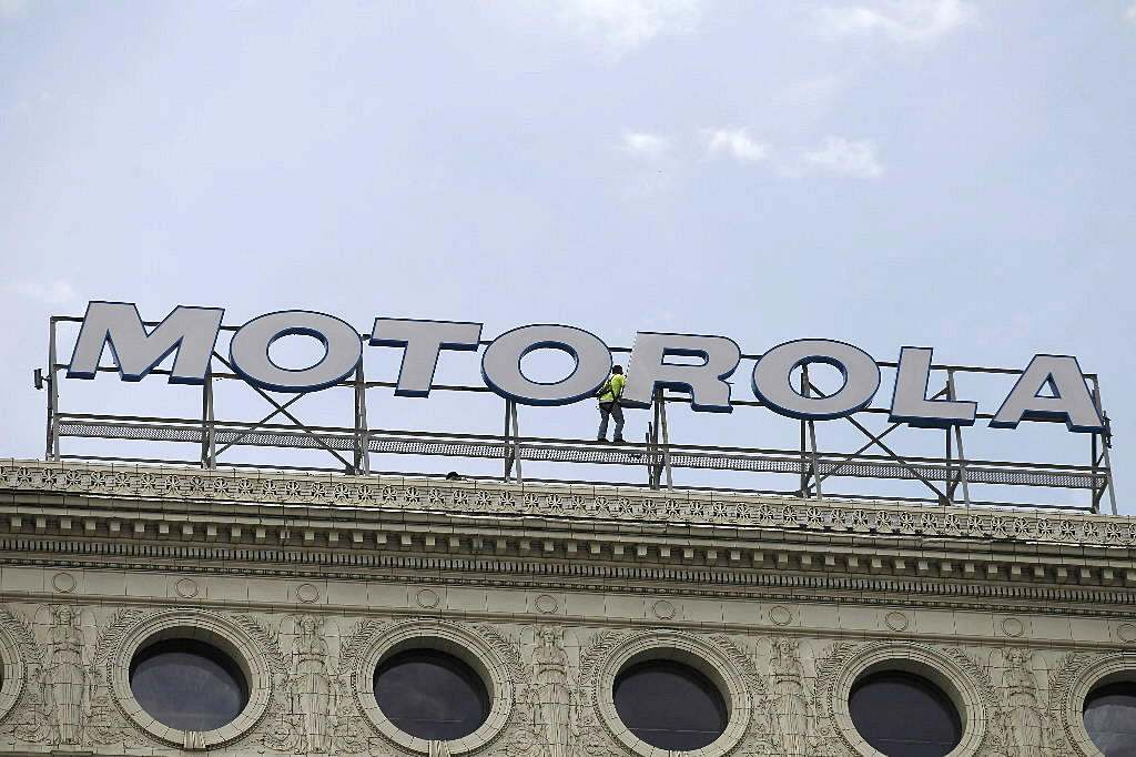 Workers finish putting a Motorola sign where the Santa Fe sign once stood atop the building at 224 S. Michigan Ave. in Chicago in 2012.