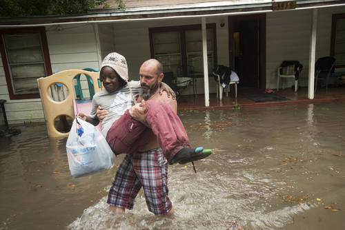 Charles Davidson helps his neighbor Santonio Coleman, 11, from his flooded home in the Kelly Ave. Basin area of Pensacola, Florida, April 30.