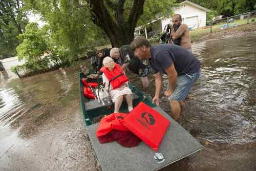 Residents help Mrs. Bray from her home as waters rise off Kelly Ave. in Pensacola, Florida, on April 30, 2014.