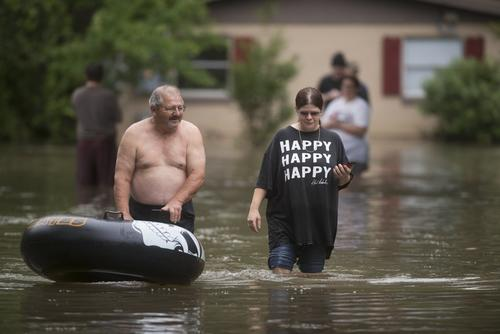 ORG XMIT: MS116 Bruce Woerner and his daughter Kelly Woerner walk to dry land in their Kelly Ave. Basin neighborhood after heavy rain in Pensacola, Florida, on April 30, 2014.