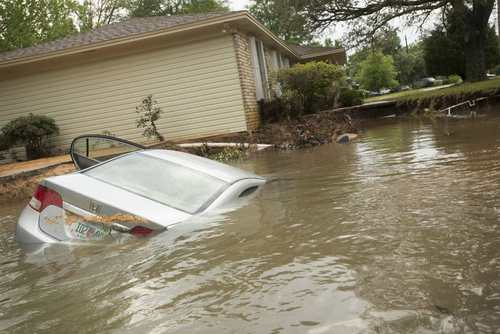 A submerged car sits in the driveway in the Cordova Park neighborhood in Pensacola, Florida, on April 30, 2014.