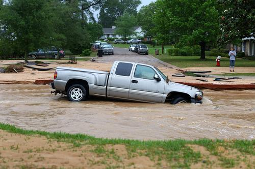 A truck is stuck in the middle of flooded Piedmont Street in the Cordova Park neighborhood after it washed out due to heavy rains on April 30, 2014 in Pensacola, Florida.