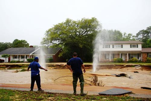 People look at natural gas leaks aas they spray into the sky on Piedmont Street in the Cordova Park neighborhood after it washed out due to heavy rains on April 30, 2014 in Pensacola, Florida.
