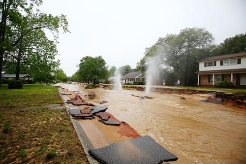Natural gas leaks spray into the sky on Piedmont Street in the Cordova Park neighborhood after it washed out due to heavy rains on April 30, 2014 in Pensacola, Florida.