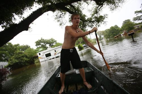 Chip Walker, 16, paddles through the flooded streets of his neighborhood in Pensacola, Florida, on April 30.