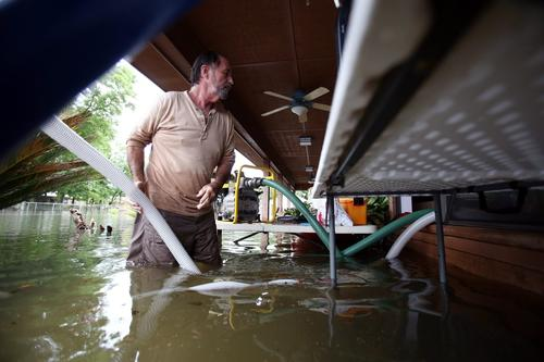Kevin Davis tries to pump water out of his flooded home in Pensacola, Florida, on April 30.