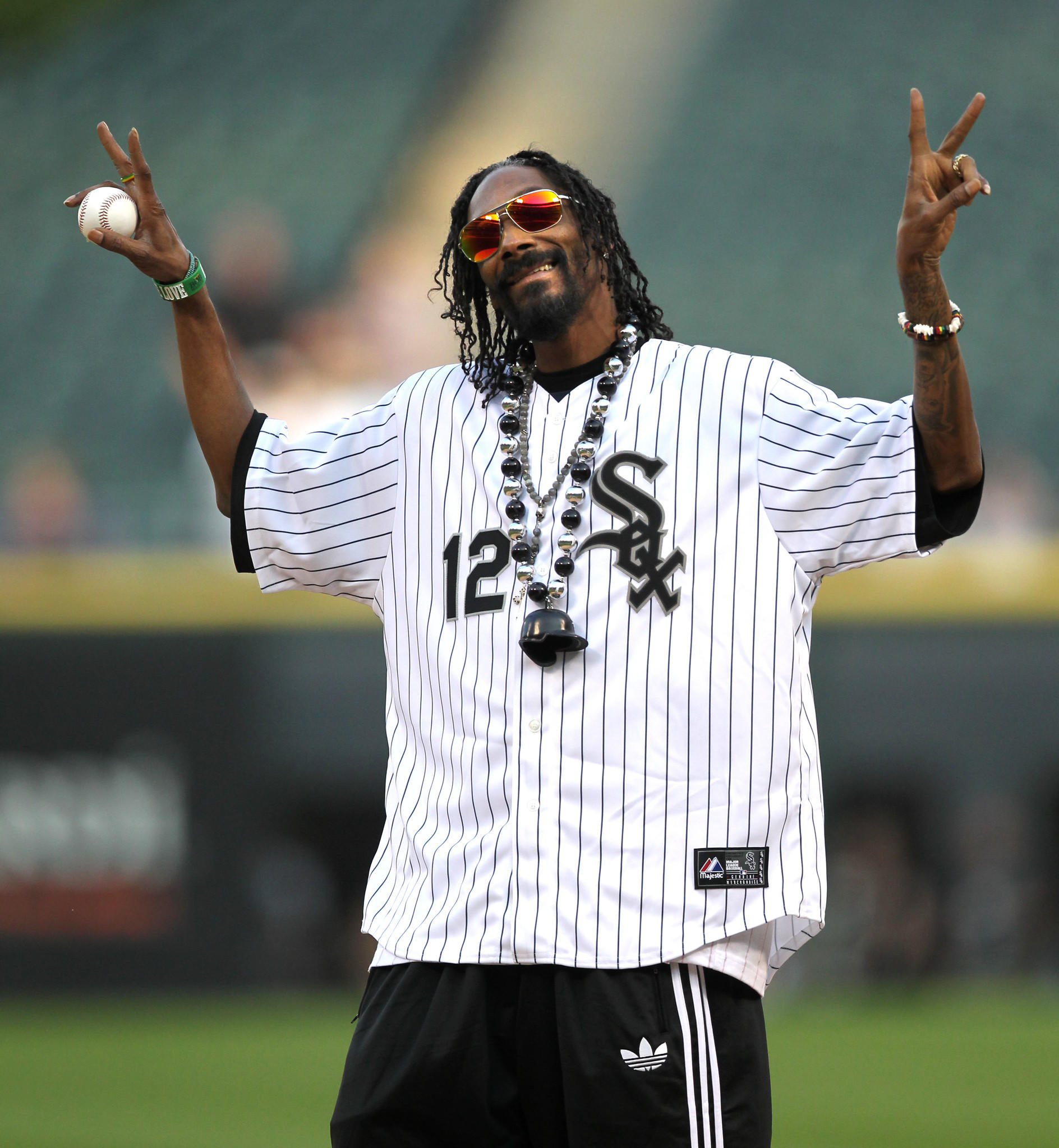 Snoop Dogg gestures to the crowd before throwing out the ceremonial first pitch before a game between the Chicago White Sox and the Minnesota Twins.