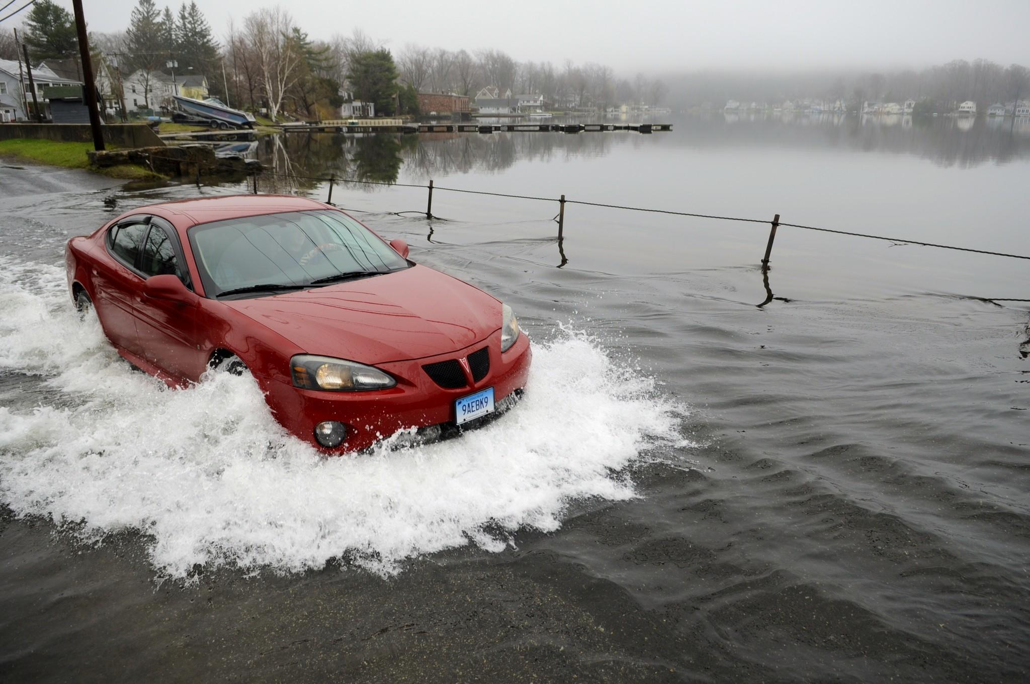 A car drives through localized flooding around Highland Lake in Winchester Thursday morning after 2-4 inches of rain hit the state the last couple days.