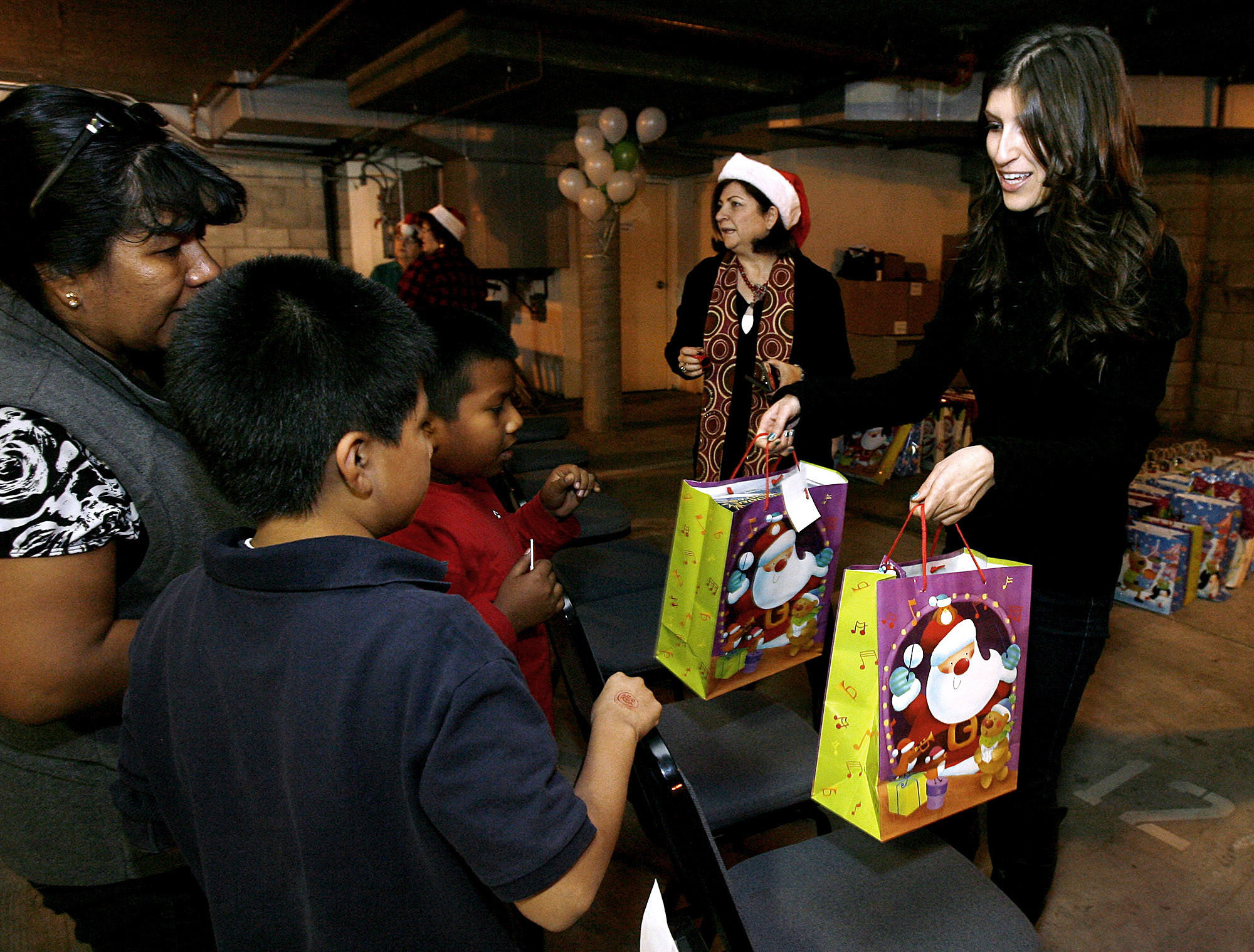 Armenian Relief Society of Western USA's Tallar Yahyayan, right, hands gifts to two local children during their annual Gift Giving Event at the company's headquarters in Glendale on December 19, 2012. Two thousand bags were expected to be given away to local children, regardless of need.The Armenian Relief Society of Western USA in Glendale, founded in 1984, is celebrating its 30th anniversary with three days of events, starting on Friday, May 2, 2014.