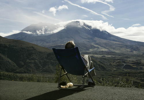 A tourist to the Cold Lake Visitor Center relaxes in the afternoon sun while watching Mount St. Helens October 7, 2004.
