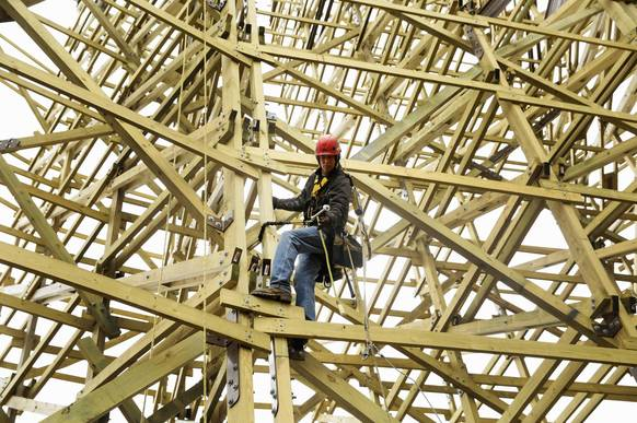 Curtis Clark catches a bolt mid-air while working up on the high bank end of the new Goliath roller coaster a