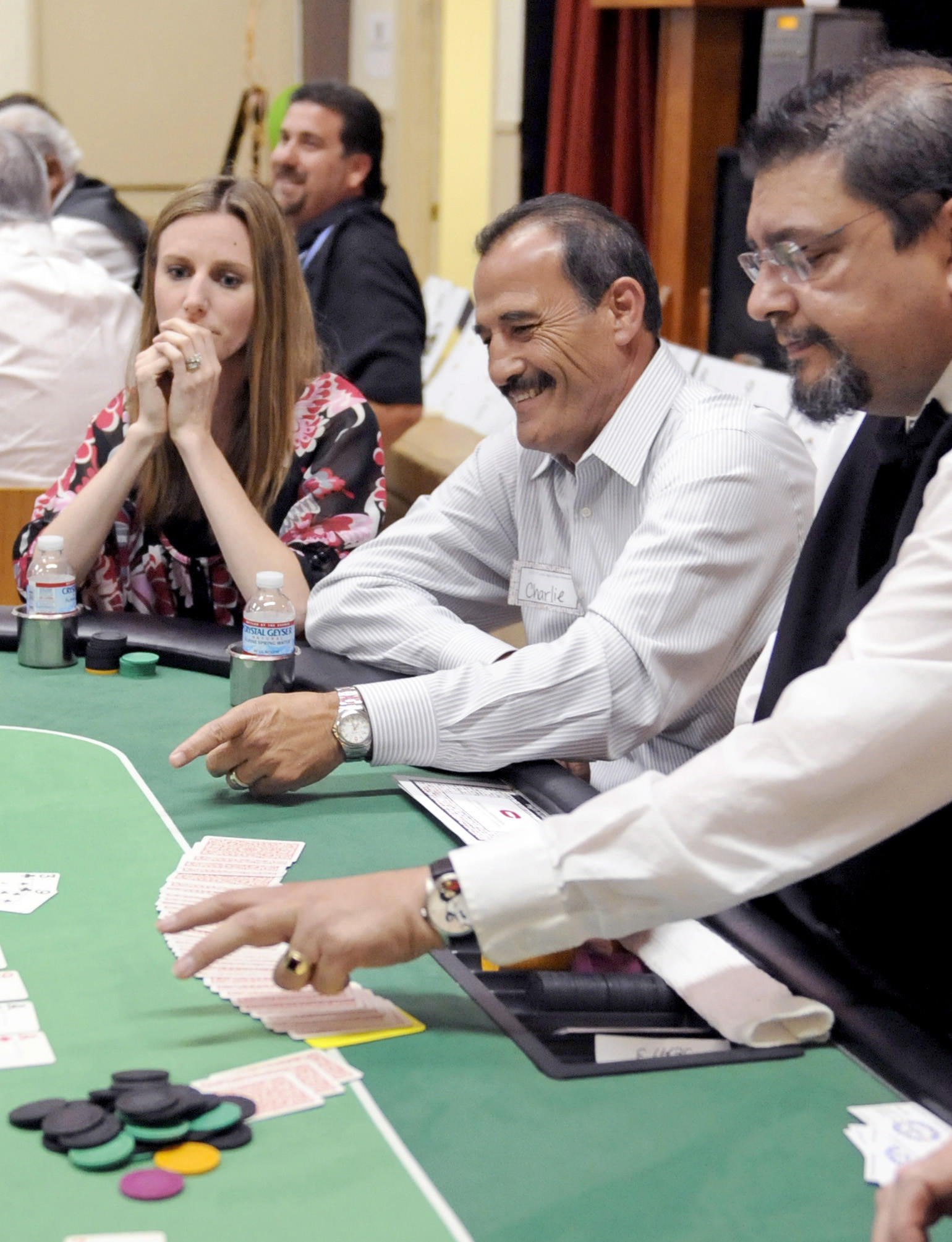 Charlie Kamar, center, smiles as he wins a hand in a poker tournament during the Casino Night at the La Cañada Flintridge Community Center on Friday, May 24, 2013 in La Cañada.