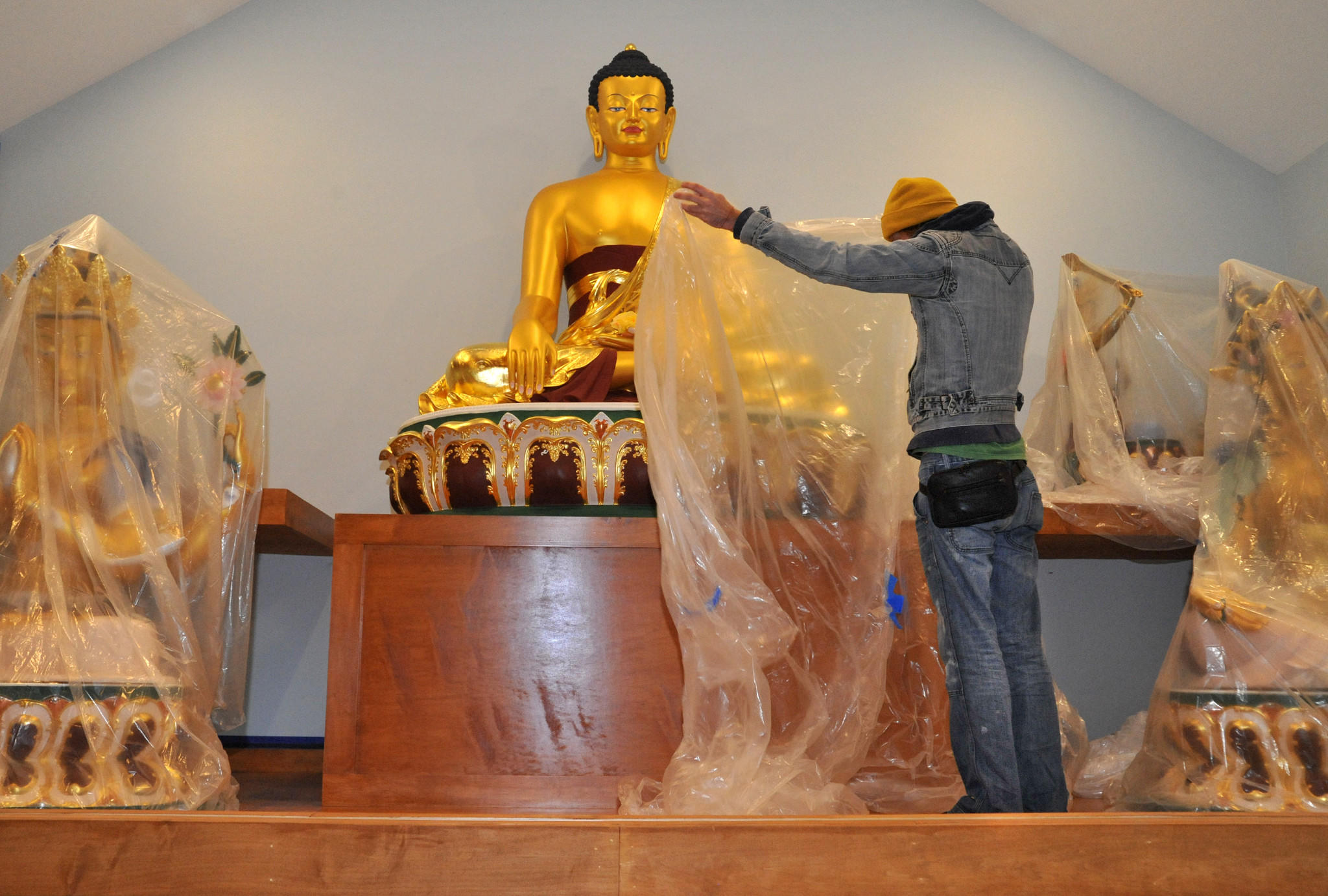 Talmadge Lazorko, who came from Florida to help with the construction of the Kadampa Medication Center Maryland, covers one of the enshrined Buddhas.